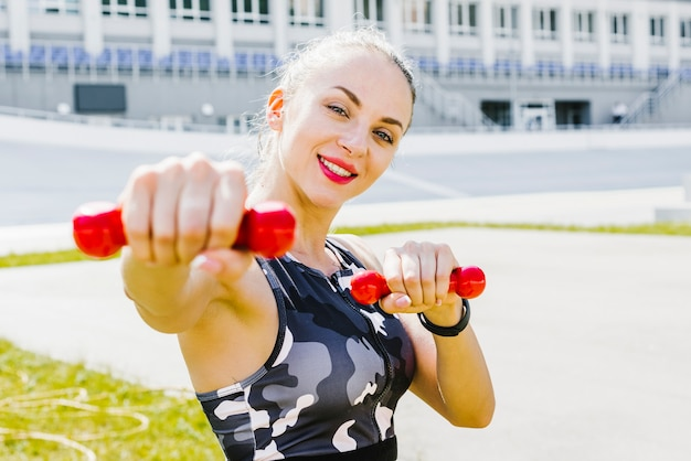 Vrouw die camera onder ogen ziet terwijl het opheffen van gewichten