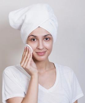 Vrouw die camera schoonmakend gezicht bekijkt