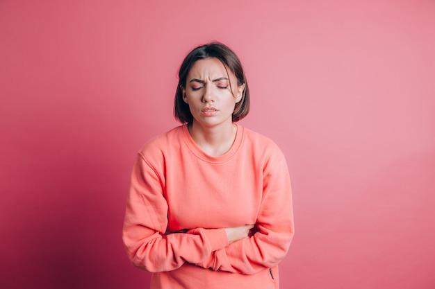 Vrouw die casual trui draagt op achtergrond die buikpijn met pijnlijke grimas lijdt, plotselinge menstruatiekrampen, gynaecologieconcept voelt