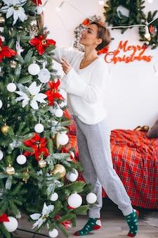 Vrouw die champaigne door kerstboom drinken
