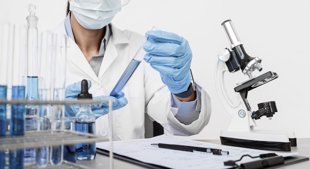 Vrouw die chemische elementen bestudeert terwijl ze een gezichtsmasker draagt