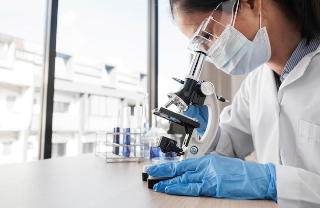 Vrouw die chemische elementen met exemplaarruimte bestudeert