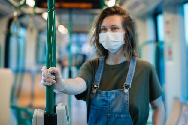 Vrouw die chirurgisch beschermend masker draagt tegen coronavurus en beschikbare handschoenen bij openbaar vervoer