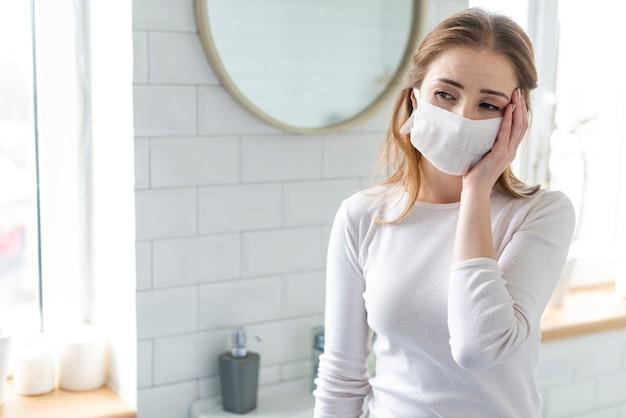 Vrouw die chirurgisch gezichtsmasker draagt dat hoofdpijn heeft
