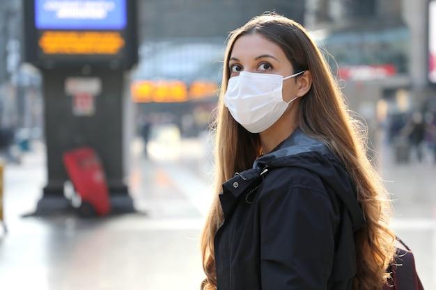 Vrouw die chirurgisch masker draagt bij treinstation dat zich zorgen maakt voor haar