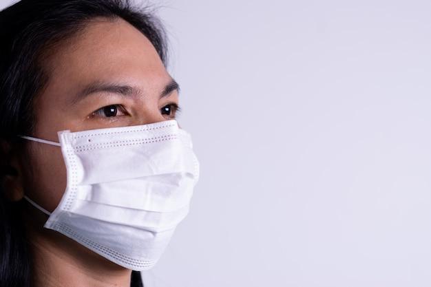 Vrouw die chirurgisch masker draagt tegen coronavirus met exemplaarruimte. coronavirus of covid-19-concept.