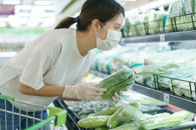 Vrouw die chirurgisch masker en handschoenen draagt, die groenten in supermarkt na pandemie coronavirus kiest.