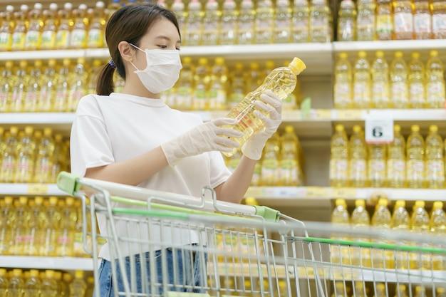 Vrouw die chirurgisch masker en handschoenen draagt, die oliefles in supermarkt koopt. paniek winkelen na een pandemie van het coronavirus.