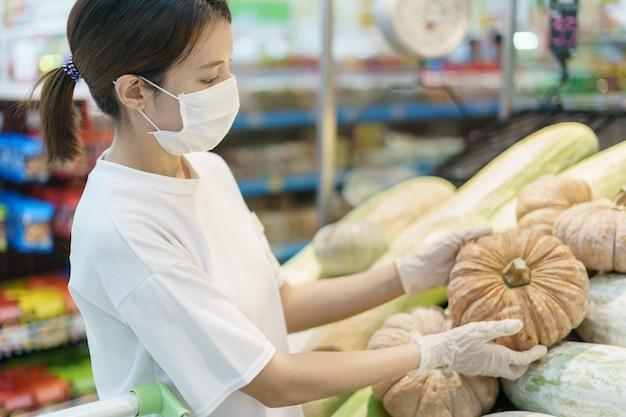 Vrouw die chirurgisch masker en handschoenen draagt, die pompoen in supermarkt koopt. paniek winkelen na een pandemie van het coronavirus.
