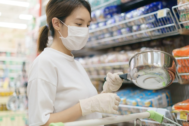 Vrouw die chirurgisch masker en handschoenen draagt, die roestvrij staalpot in supermarkt koopt. paniek winkelen na een pandemie van het coronavirus.