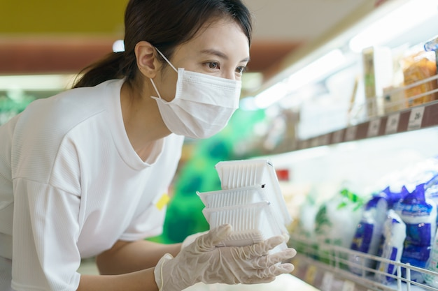 Vrouw die chirurgisch masker en handschoenen draagt, die tofu in supermarkt na pandemie coronavirus kiest.