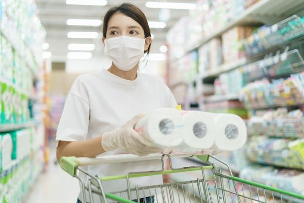 Vrouw die chirurgisch masker en handschoenen draagt, die toiletpapierbroodje in supermarkt koopt. paniek winkelen na een pandemie van het coronavirus.