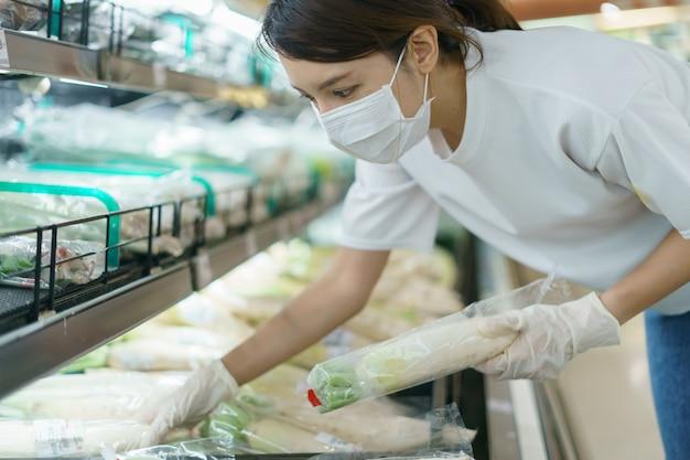 Vrouw die chirurgisch masker en handschoenen draagt, die witte radijs in supermarkt na pandemie coronavirus kiest.
