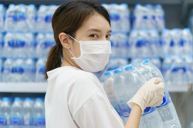 Vrouw die chirurgisch masker en handschoenen draagt, drinkwater in supermarkt koopt. paniek winkelen na een pandemie van het coronavirus.