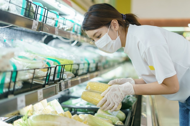 Vrouw die chirurgisch masker en handschoenen dragen, die graan in supermarkt na pandemie coronavirus kiezen.