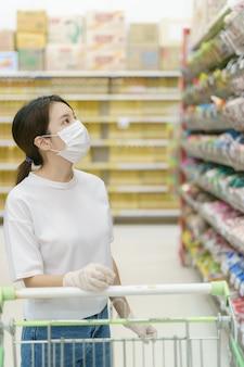 Vrouw die chirurgisch masker en handschoenen met een boodschappenwagentje draagt, dat tijdens een pandemie van coronavirus winkelt.