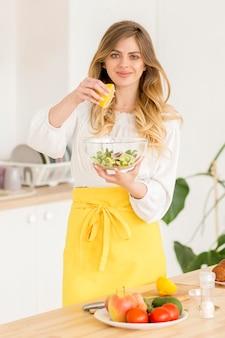 Vrouw die citroensap op salade zet