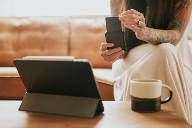 Vrouw die contante betaalkaartlezer gebruikt voor haar kleine bedrijf thuis