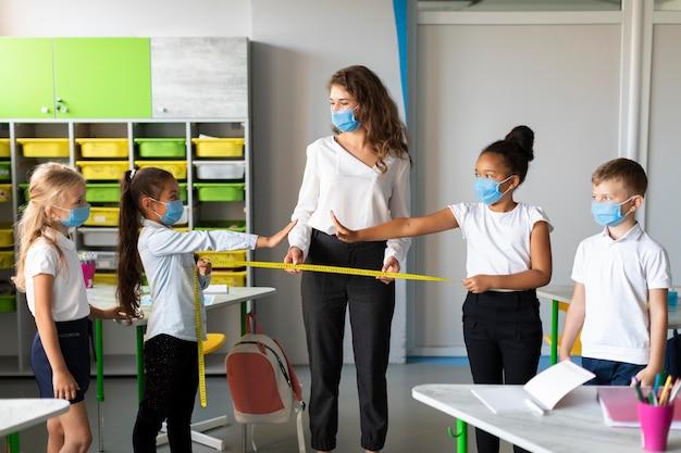 Vrouw die covid-preventie aan kinderen onderwijst