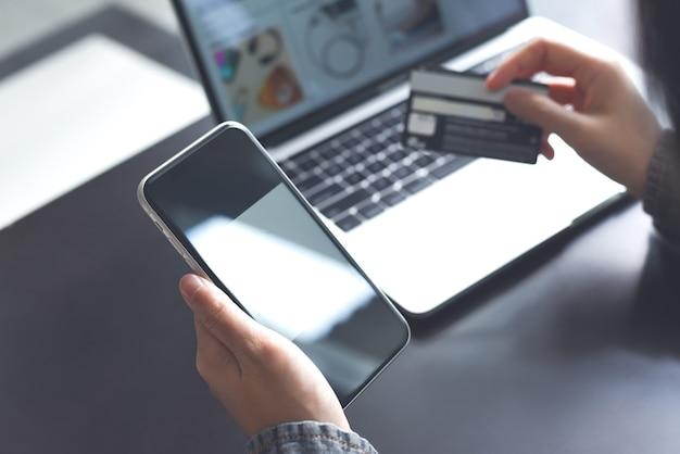 Vrouw die creditcard en mobiele telefoon gebruikt voor online winkelen en digitaal bankieren