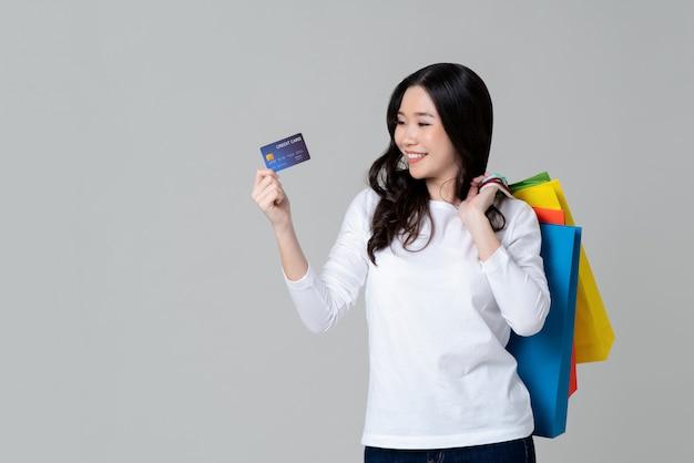 Vrouw die creditcard toont en het winkelen zakken draagt