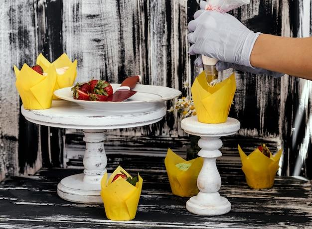 Vrouw die cupcakesaardbei verfraait. foto van proces. zelfgemaakte muffins.