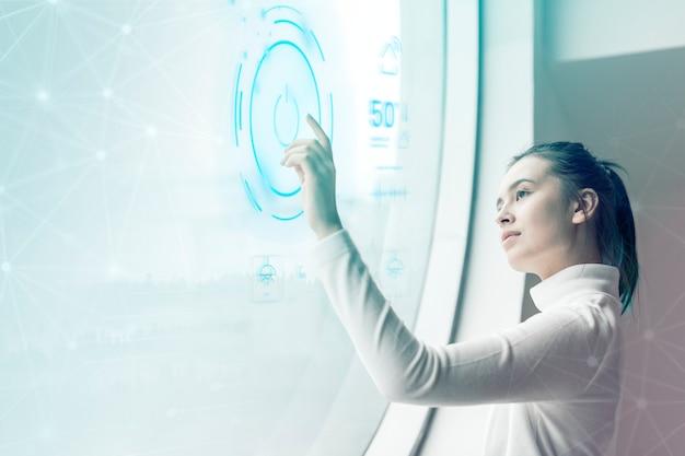 Vrouw die de aan / uit-knop op het virtuele scherm slimme huistechnologie aanraakt