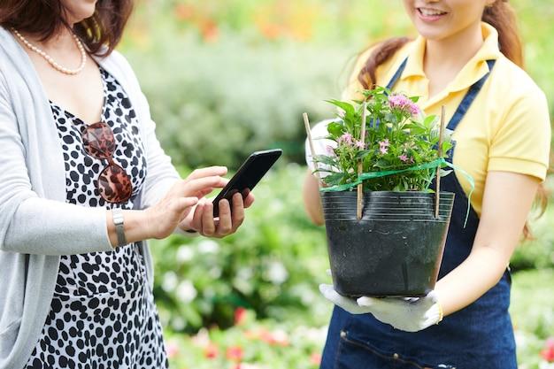 Vrouw die de app voor het zoeken naar bloemen gebruikt