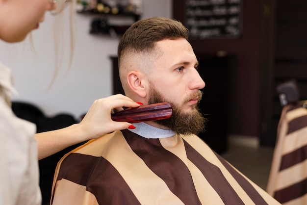 Vrouw die de baard van een man borstelt