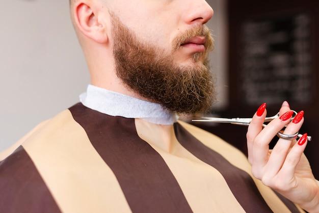 Vrouw die de baard van een man snijdt bij een professionele kapperswinkel