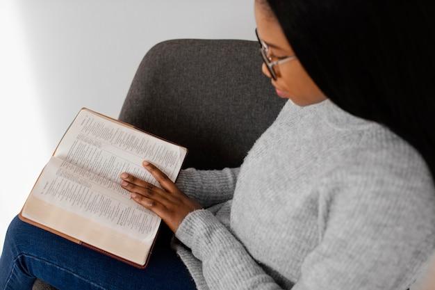 Vrouw die de bijbel binnenshuis leest