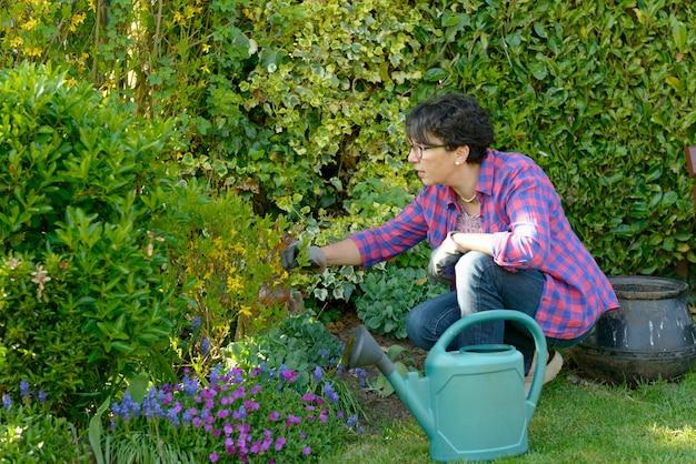 Vrouw die de bloemen in haar mooie tuin tuinieren.