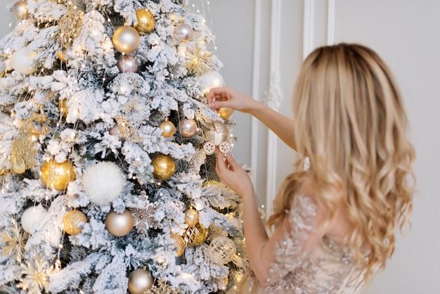 Vrouw die de boom van het nieuwjaar verfraait. kerstboom speelgoed in de vorm van een kinderwagen.