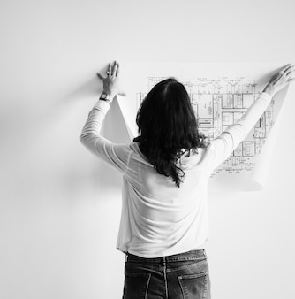 Vrouw die de bouwblauwdruk op de muur toont