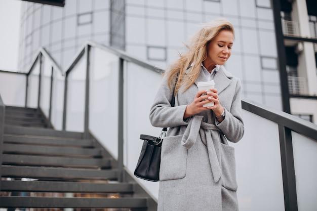 Vrouw die de brug oversteekt en koffie drinkt