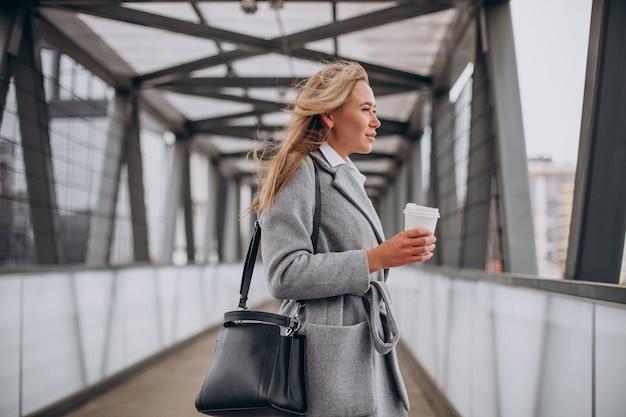 Vrouw die de brug oversteekt en koffie drinkt Gratis Foto