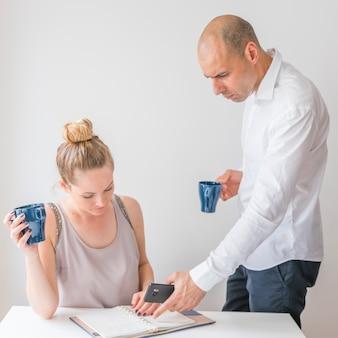 Vrouw die de calculator bekijken die van de zakenmanholding op agenda richten