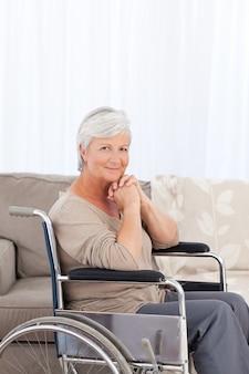 Vrouw die de camera in haar rolstoel bekijkt