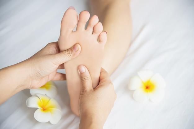 Vrouw die de dienst van de voetmassage van masseuse ontvangt dichtbij dichtbij en voet - ontspan in het concept van de de therapiedienst van de voetmassage