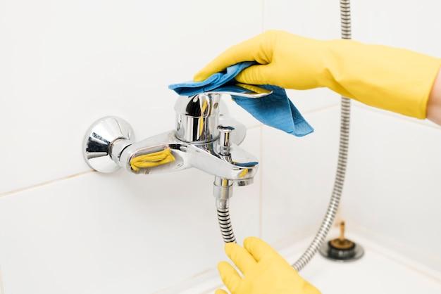 Vrouw die de douche schoonmaakt