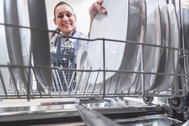 Vrouw die de gerechten in de vaatwasser in de keuken van haar appartement