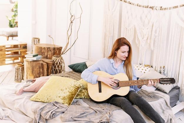 Vrouw die de gitaar op het bed speelt