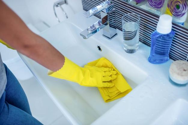 Vrouw die de gootsteen in de badkamers schoonmaakt