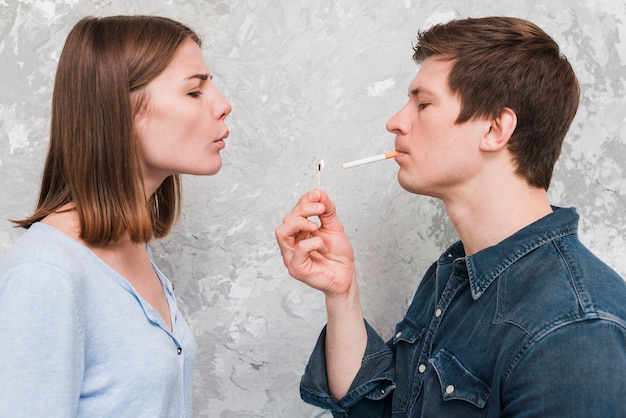 Vrouw die de greep van de greepstok door haar vriend dragende sigaret in mond blaast