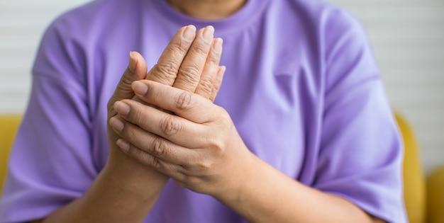 Vrouw die de hand gebruikt om de andere hand vast te houden met pijn, pijn en tintelingen. concept van guillain barre-syndroom en gevoelloze handenziekte.