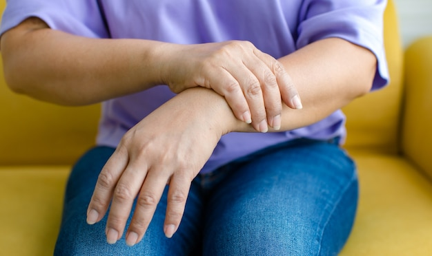 Vrouw die de hand gebruikt om haar arm vast te houden met pijn, pijn en tintelingen. concept van guillain barre-syndroom en gevoelloze handenziekte.