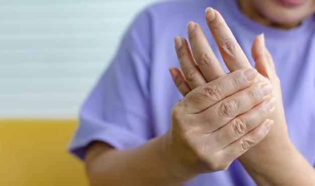 Vrouw die de hand gebruikt om haar handpalm vast te houden met pijn, pijn en tintelingen. concept van guillain barre-syndroom en gevoelloze handenziekte.