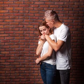 Vrouw die de hand van haar vriend met exemplaarruimte kust