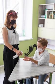 Vrouw die de handen van haar student desinfecteert