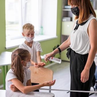 Vrouw die de handen van haar studenten desinfecteert